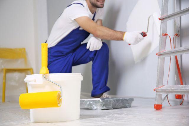 Un uomo con un tuta blu mentre imbianca un muro