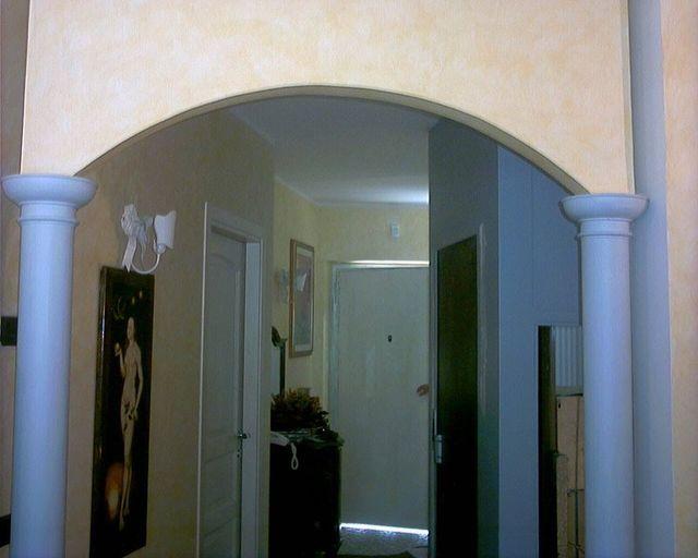 Un corridoio con una arcata e delle colonne bianche all'interno di una casa