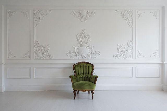 una stanza con dei pareti decorate di color bianco e una poltrona verde