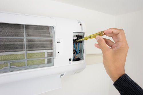una mano sta verificando la presenza di corrente elettrica in un condizionatore a muro