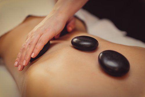 schiena di una donna alla quale viene fatto un massaggio con le pietre calde