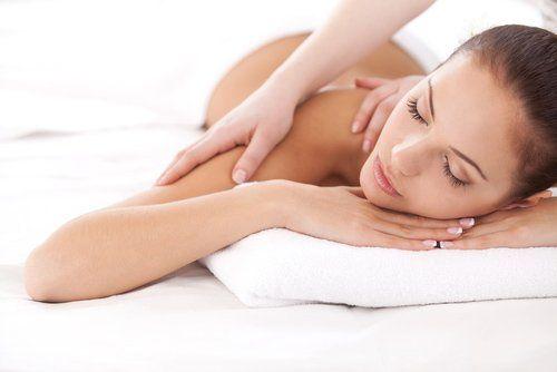 donna sdraiata alla quale viene fatto un massaggio