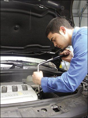 A trinaed technician fixing a car