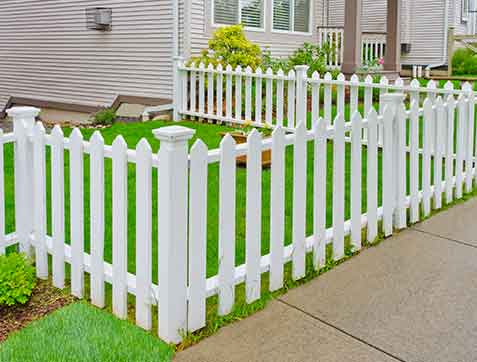 White wooden country style fence and small yard behind