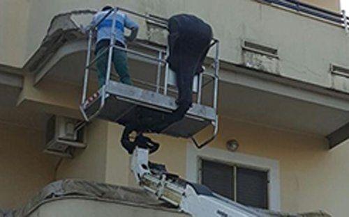 Due operai su una piattaforma elevatrice al lavoro su una parete esterna