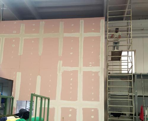 Operaio su impalcatura lavora su una grande parete interna