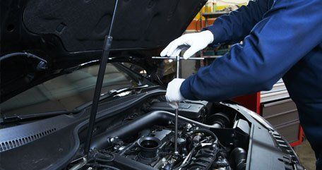 Mechanic in white gloves, working on an engine