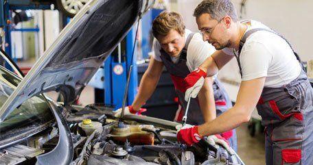Two mechanics working on a car engine