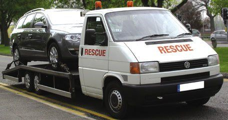 A car on the back of a recovery truck