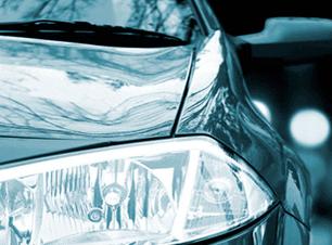 Front headlamp of a dark green car