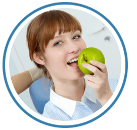 A young lady about to bite into an apple