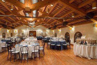 vista interna di un ristorante con soffitto in legno e tavoli apparecchiati  per festa
