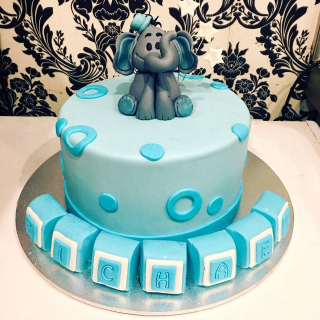 blue christening cake with elephant on top and name in block letters