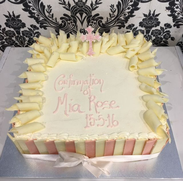 white confirmation cake with pink panels and cross