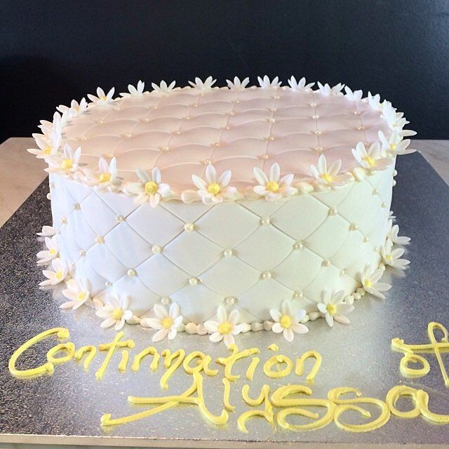 white pillow effect confirmation cake with white and yellow flower accents