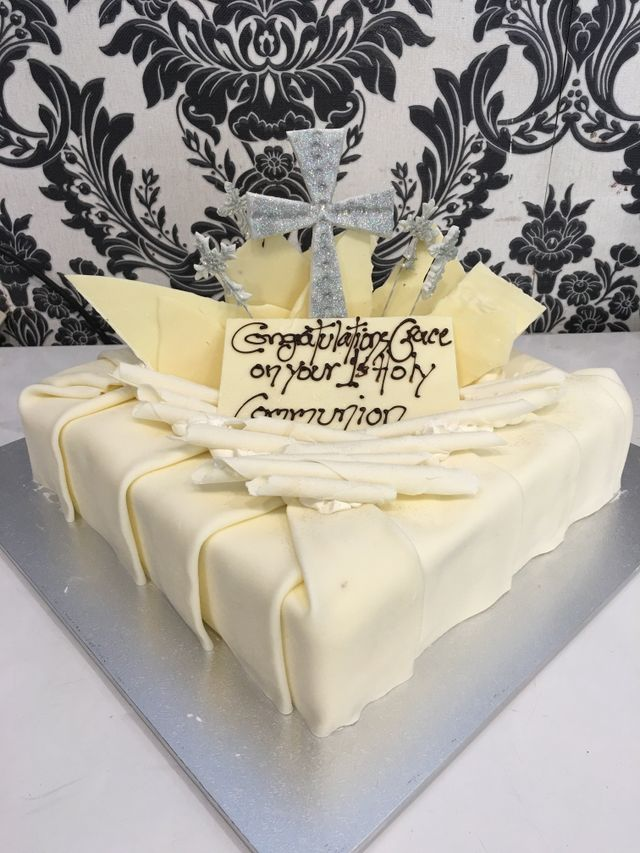 white holy communioncake with silver cross on top and blue panels