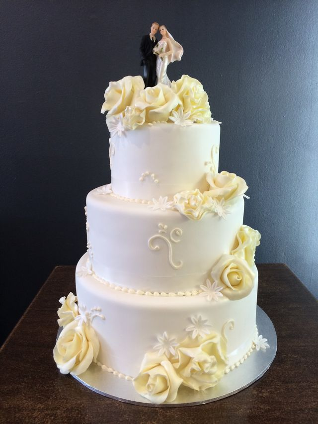 white pillow effect cake with macaron tower on top