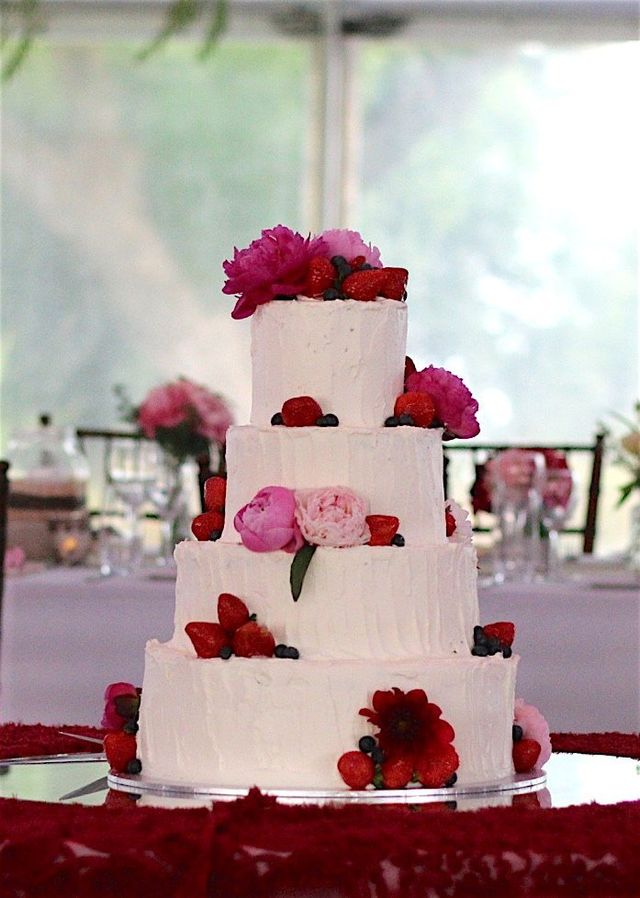 four level white cake with red roses strategically placed