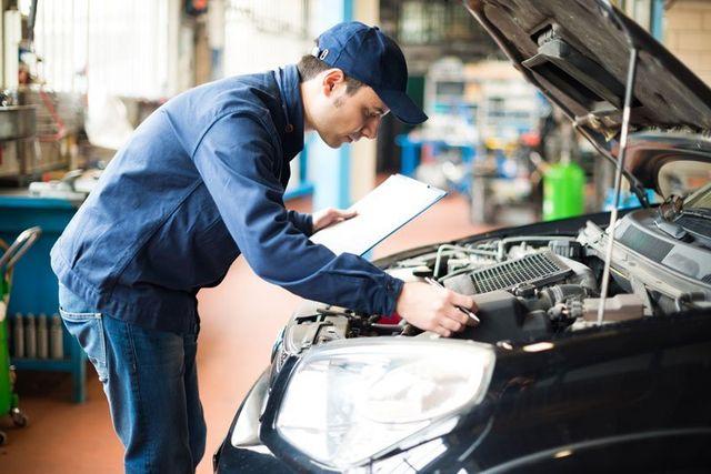 un meccanico con una tuta blu e un cappello ha in mano una scheda tecnica e sta guardando il motore di una vettura