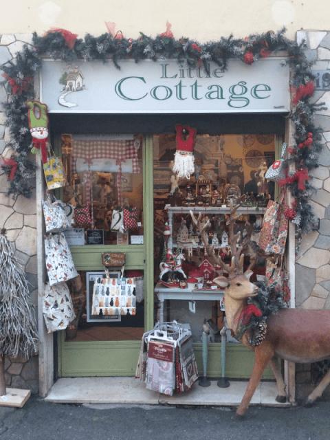 vetrina di negozio con articoli da regali e insegna con scritto LITTLE COTTAGE c