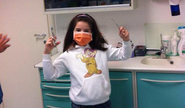 una bambina con una mascherina arancione con in mano una pinza e un rampino da dentista