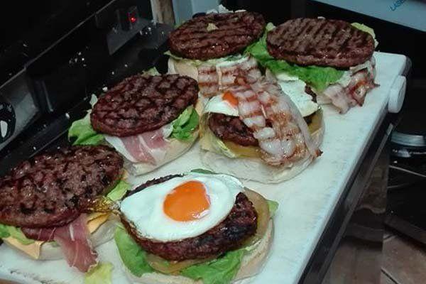 degli hamburger con uovo, carne e insalata