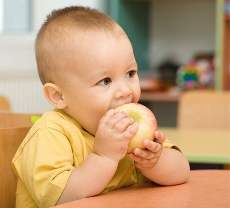 a small kid eating apple