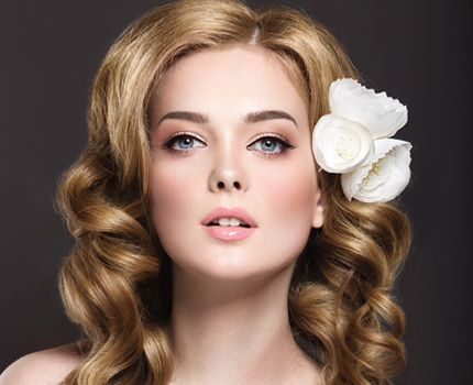 A model with blonde wavy hair and three flowers in her hair
