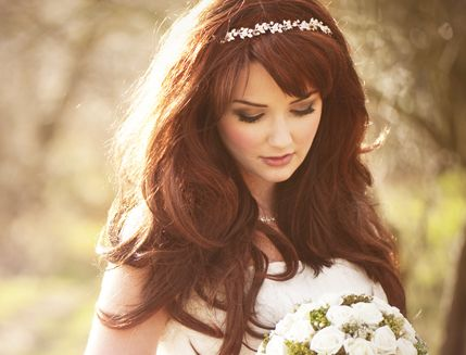 A bride with long dark hair and a sparkly headband