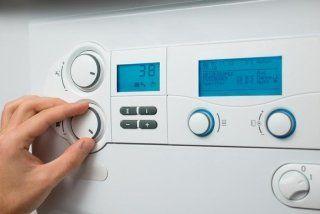 una mano che regola la temperatura con un termostato
