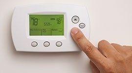 un dito che preme i tasti di un termostato