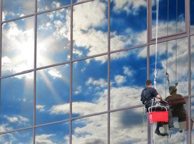 uomo appeso che lava vetrate esterne di un ufficio