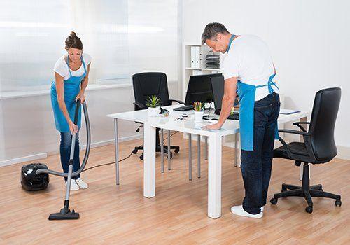 una donna con una scopa elettrica e un uomo che pulisce una scrivania di un ufficio