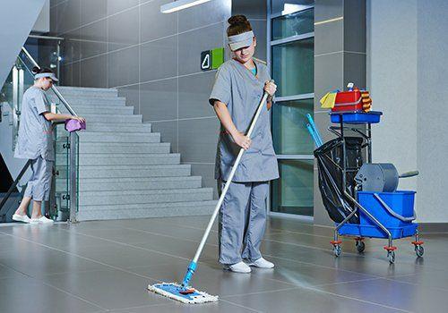 delle inservienti che puliscono per terra con un mocio