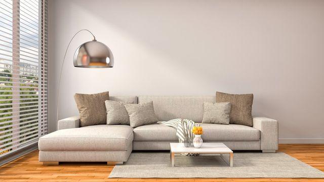 Vista di un soggiorno con il divano e tappeto. DR Tendaggi a Marina di Gioiosa Ionica