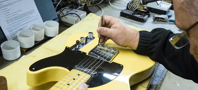 Man fixing guitar