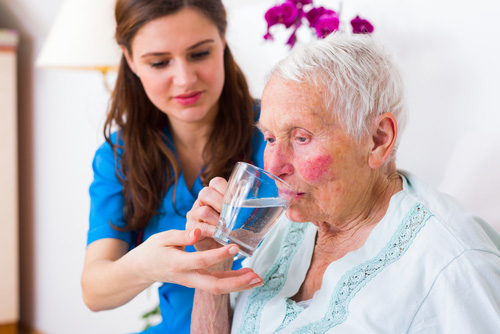 persona dello staff aiuta una donna anziana a bere