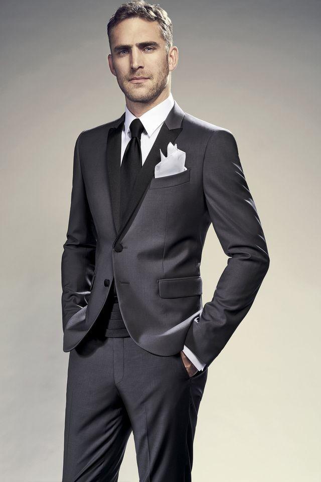 un uomo con dei pantaloni di color grigio e una giacca di color nero
