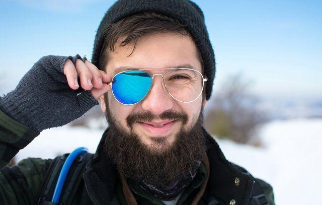 un ragazzo che indossa un paio di occhiali da vista senza una lente sorridendo