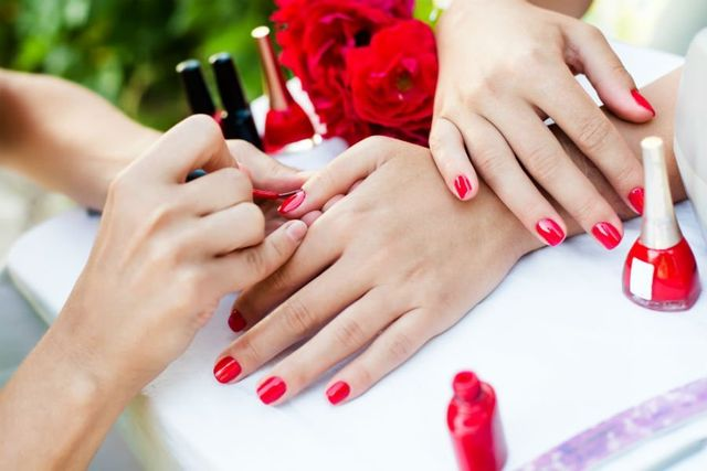 Manicure ed estetista che mette smalto rosso ad una ragazza