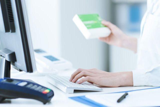una donna con camice bianco, con la mano sinistra scrive al computer e con la destra tiene in mano una confezione di un medicinale