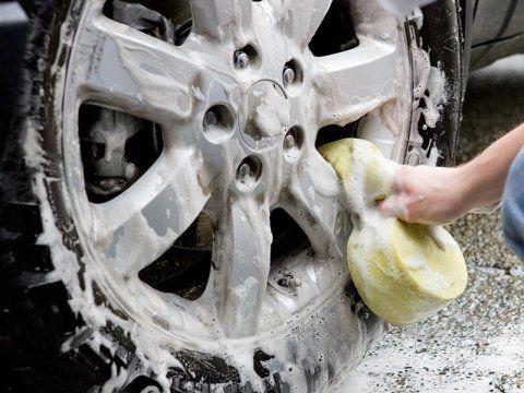 Tecnico officina che lava cerchioni delle ruote auto con spugna