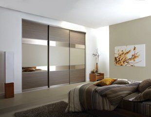 Bedroom with neutral colour scheme and fitted sliding wardrobe