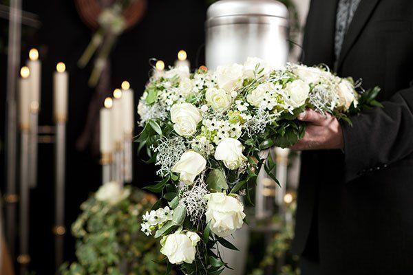 un uomo in un completo nero con un bouquet di fiori