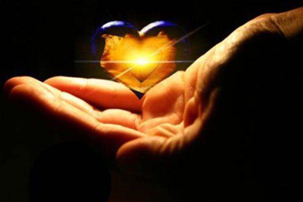una mano e un disegno a forma di cuore con una luce