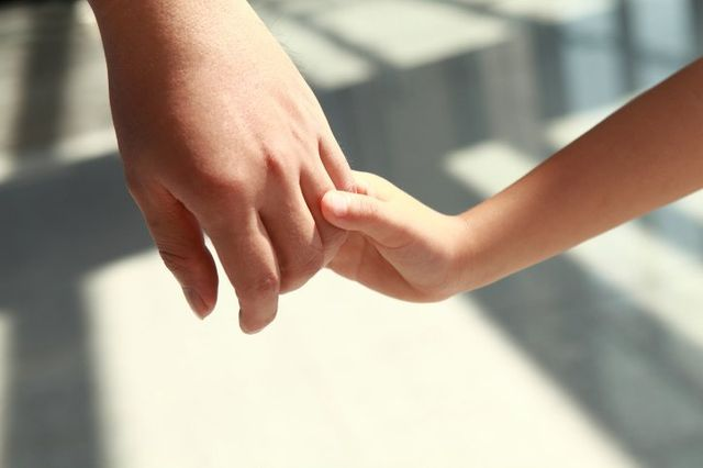 Close up of child holding hand