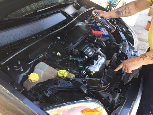 una mano che spruzza del lubrificante in un motore di una macchina