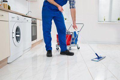 uomo con tuta da lavoro pulisce un pavimento