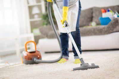 persona che usa un aspirapolvere su un tappeto