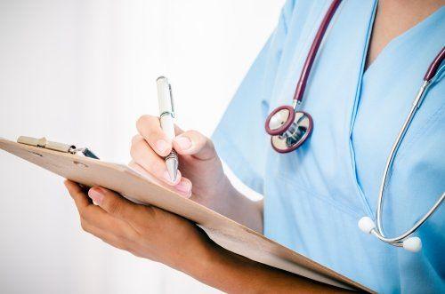 Medico che annota qualcosa su un foglio